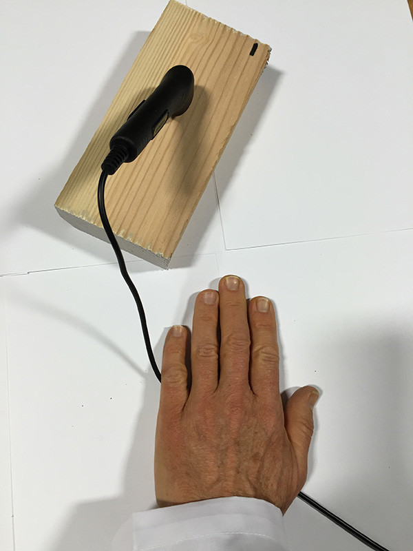 Picture of hand pressing down on a pin meter cable with meter in a block of wood