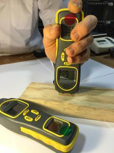 Photo of hand holding a moisture meter to piece of wood, with second moisture meter laying in foreground